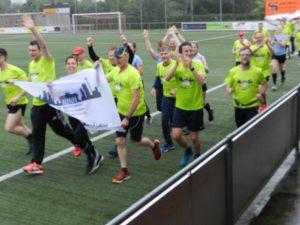 De lopers stormen in de gietende regen het voetbalveld op, terwijl de streetband vrolijk speelt