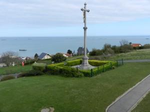 Een kruisbeeld kijkt in Arromanches uit over de zee waarin nog hier en daar een betonnen bak te zien is van de kunstmatige haven.